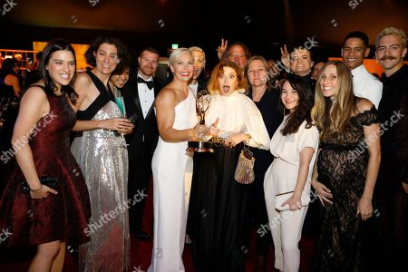 "Stock Picture of Natasha Lyonne, Jennifer Rogien. Natasha Lyonne, center, poses with Jennifer Rogien, fifth from left, winner of the award for outstanding contemporary costumes, and the team from ""Russian Doll"" at the Governors Ball during night two of the Television Academy's 2019 Creative Arts Emmy Awards, at the Microsoft Theater in Los Angeles"