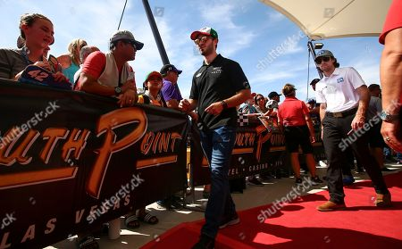 Daniel Suarez, center, and Ryan Blaney, right, walk by fans before a NASCAR Cup Series auto race at the Las Vegas Motor Speedway on