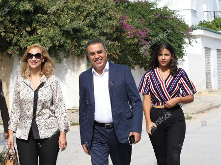Presidential candidate Mehdi Jomaa (C) accompagned by his wife Hele (L), arrives to cast his ballot for presidential election at a polling station in Tunis