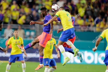 Brazil midfielder Casemiro (5) heads the ball as Colombia defender William Tesillo (6) defends during the second half of a friendly soccer match, in Miami Gardens, Fla. The game ended in a 2-2 tie