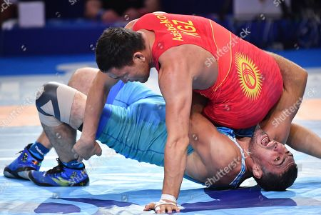 Denis Maksymilian Kudla, Mikalai Stadub, Rustam Assakalov, Atabek Azisbekov. Rustam Assakalov of Uzbekistan, bottom, and Atabek Azisbekov of Kyrgyzstan compete in the bronze match of the men's Greco-Roman 87kg category of the Wrestling World Championships in Nur-Sultan, Kazakhstan