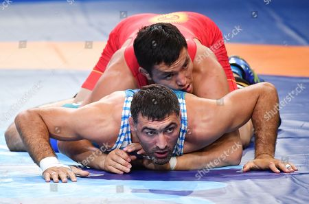 Denis Maksymilian Kudla, Mikalai Stadub, Rustam Assakalov, Atabek Azisbekov. Rustam Assakalov of Uzbekistan and Atabek Azisbekov of Kyrgyzstan, top, compete in the bronze match of the men's Greco-Roman 87kg category of the Wrestling World Championships in Nur-Sultan, Kazakhstan
