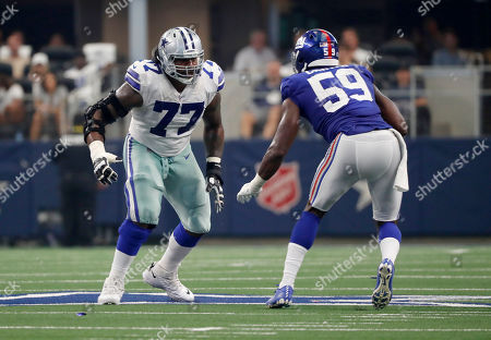 Dallas Cowboys offensive tackle Tyron Smith, 77, faces off against New York Giants linebacker Lorenzo Carter, 59, during the first half of an NFL football game in Arlington, Texas