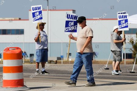 James Hatfield, center, carries a picket sign with other striking workers outside the General Motors plant in Spring Hill, Tenn., . More than 49,000 members of the United Auto Workers went on strike Monday against General Motors, bringing more than 50 factories and parts warehouses to a standstill in the union's first walkout against the No. 1 U.S. automaker in over a decade