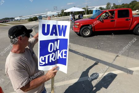 James Hatfield waves to a passing driver as he pickets outside the General Motors plant in Spring Hill, Tenn., . More than 49,000 members of the United Auto Workers walked off General Motors factory floors or set up picket lines early Monday as contract talks with the company deteriorated into a strike