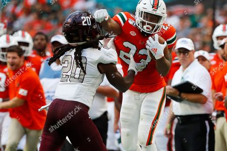 Stock Picture of Bethune Cookman cornerback Trevor Merritt (20) attempts to stop Miami running back Cam'Ron Harris (23) during the first half of an NCAA college football game, in Miami Gardens, Fla