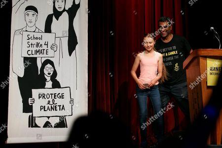 Stock Photo of Greta Thunberg, Kumi Naidoo. Swedish climate activist Greta Thunberg, 16, left, walks with Amnesty International Secretary General Kumi Naidoo, as she accepts the Ambassador of Conscience Award from the organization, during an event at George Washington University, in Washington. The award is the organization's highest honor for human rights work