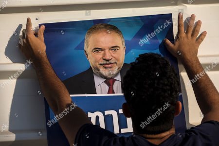 Israeli supporter of the leader of the Yisrael Beiteinu (Israel Our Home) right-wing nationalist party Avigdor Liberman hangs election poster outside the polling station, in the settlement of Nokdim, West Bank