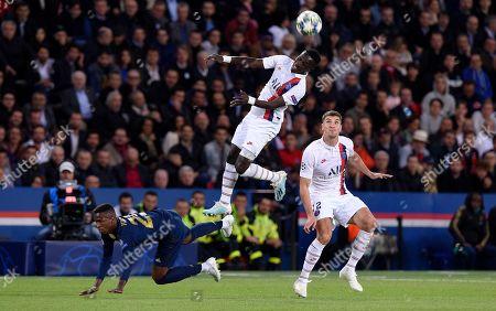 Idrissa Gueye of Paris Saint-Germain beats Vinicius Junior of Real Madrid to the ball as Thomas Meunier looks on