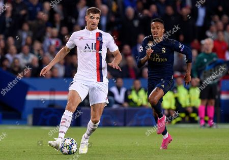 Thomas Meunier of Paris Saint-Germain knocks the ball past Raphael Varane of Real Madrid as Eder Militao looks on