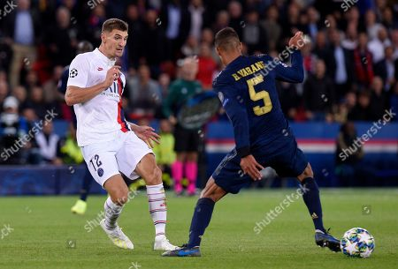 Thomas Meunier of Paris Saint-Germain knocks the ball past Raphael Varane of Real Madrid