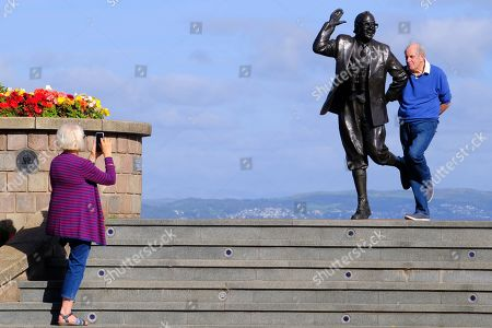 Visitors to the seaside resort of Morecambe pose by the statue of comedian Eric Morecambe as sunshine continues across the country.