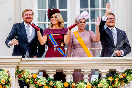 King Willem-Alexander, Queen Maxima, Prince Constantijn and Princess Laurentien wave to bystanders from the balcony at Noordeinde Palace