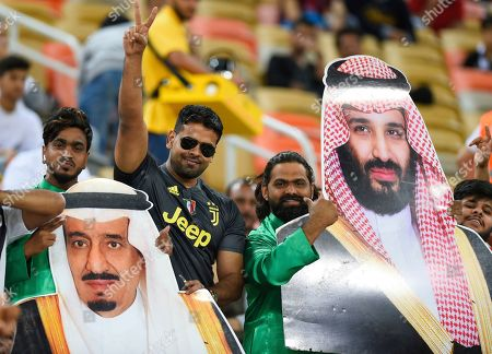 Saudi fans holds pictures of Saudi Arabia's King Salman, left, and Saudi Crown Prince Mohammed bin Salman ahead of the Italian Super Cup final soccer match between AC Milan and Juventus at King Abdullah stadium in Jiddah, Saudi Arabia. Amnesty International and the journalists union for Italian state TV RAI have written a joint letter to the presidents of Juventus and Lazio asking the clubs not to the play the Italian Super Cup in Saudi Arabia due to human rights abuses