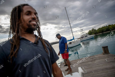 "David Murray, president of the Oracabessa Fishers Association and warden for the Oracabessa Fish Sanctuary, stands on the dock with sanctuary manager Inilek Wilmont in Oracabessa Bay, Jamaica, . ""Most people, what they see, and why people have bought into it is walking down to the beach and looking into the water and seeing fish you know,"" said Wilmot of the sanctuary's success with the local fishermen"