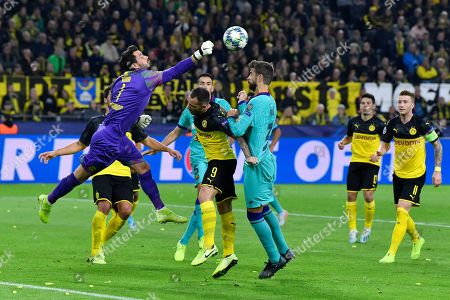 Dortmund's goalkeeper Roman Burki, left, clears the ball during in front Barcelona's Gerard Pique during the Champions League Group F soccer match between Borussia Dortmund and FC Barcelona in Dortmund, Germany