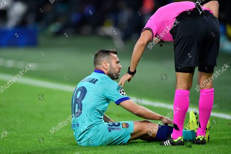 Referee Ovidiu Hategan speaks with Barcelona's Jordi Alba after he gots injured during the Champions League Group F soccer match between Borussia Dortmund and FC Barcelona in Dortmund, Germany