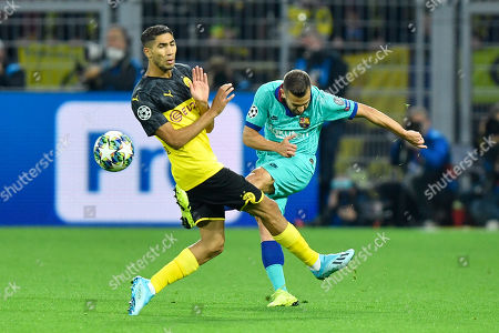 Stock Image of Barcelona's Jordi Alba, right, clears the ball in front Dortmund's Achraf Hakimi during the Champions League Group F soccer match between Borussia Dortmund and FC Barcelona in Dortmund, Germany