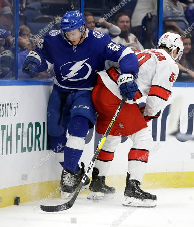 Stock Picture of Ben Thomas, Janne Kuokkanen. Tampa Bay Lightning defenseman Ben Thomas (56) and Carolina Hurricanes left wing Janne Kuokkanen (59) fight for a loose puck during the first period of an NHL preseason hockey game, in Tampa, Fla