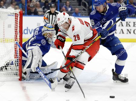 Brian Gibbons, Scott Wedgewood, Ben Thomas. Carolina Hurricanes center Brian Gibbons (29) reaches for a rebound in front of Tampa Bay Lightning defenseman Ben Thomas (56) and goaltender Scott Wedgewood (29) during the first period of an NHL preseason hockey game, in Tampa, Fla