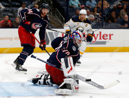 Columbus Blue Jackets goalie Joonas Korpisalo, foreground, of Finland, makes a stop between Buffalo Sabres forward Kyle Okposo, right, and Blue Jackets defenseman Vladislav Gavrikov, of Russia, during the first period of an NHL preseason hockey game in Columbus, Ohio