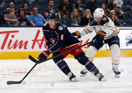 Columbus Blue Jackets defenseman Zach Werenski, left, controls the puck against Buffalo Sabres forward Kyle Okposo during the third period of an NHL preseason hockey game in Columbus, Ohio, . The Blue Jackets won 4-1