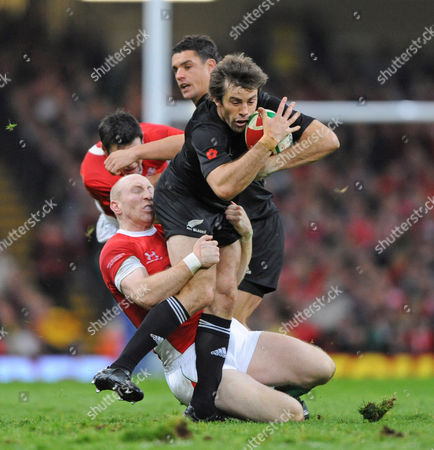 Conrad Smith of New Zealand  is tackled by Tom Shanklin of Wales