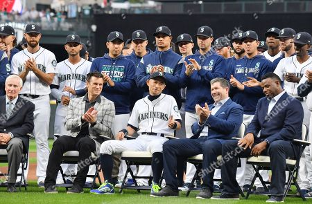 Former Seattle Mariners player Ichiro Suzuki (center) reacts as general manager Jerry Dipoto, Mariners legend Edgar Martinez and Ken Griffey, Jr., applaud during a ceremony honoring Suzuki with the franchise achievement award before before the Major League Baseball game at T-Mobile Park
