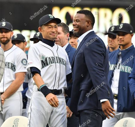 Former Seattle Mariners player Ichiro Suzuki (L)  reacts with Ken Griffey, Jr., applaud during a ceremony honoring Suzuki with the franchise achievement award before the Major League Baseball game at T-Mobile Park