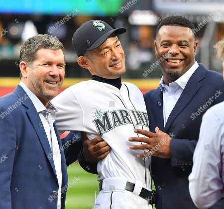 Former Seattle Mariners player Ichiro Suzuki (center) reacts as Mariners legend Edgar Martinez (L) and Ken Griffey, Jr., applaud during a ceremony honoring Suzuki with the franchise achievement award before the Major League Baseball game at T-Mobile Park