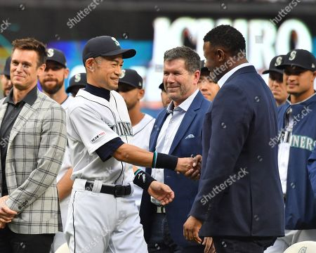 Former Seattle Mariners player Ichiro Suzuki shakes hands with Ken Griffey, Jr., applaud during a ceremony honoring Suzuki with the franchise achievement award before the Major League Baseball game at T-Mobile Park