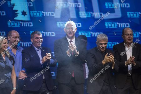 Blue and White party leaders, from the left, Gabi Ashkenazi, Benny Gantz, (center), Yair Lapid and Gabi Ashkenazi greet their supporters at party headquarters after the first results of the elections