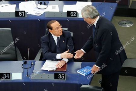"""Italy's Antonio Tajani, right, greets Silvio Berlusconi during a session at the European Parliament in Strasbourg, eastern France. The risk of Britain leaving the European Union without a divorce deal remains """"very real,"""" European Commission chief Jean-Claude Juncker declared Wednesday as EU lawmakers debated the ramifications of a no-deal Brexit"""