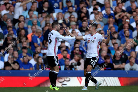 John Egan and Chris Basham of Sheffield United celebrate the own goal scored by Yerry Mina of Everton