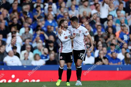 Stock Image of John Egan and Chris Basham of Sheffield United celebrate the own goal scored by Yerry Mina of Everton