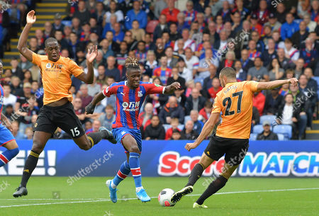 Romain Saiss of Wolverhampton Wanderers ahead of Wilfried Zaha of Crystal Palace as Willy Boly of Wolverhampton Wanderers takes evasive action
