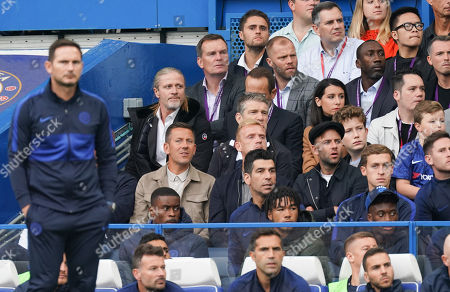 Former Chelsea forward players, Jimmy Floyd Hasselbaink, Eidur Gudjohnsen, and Emanuel Petit sit in the seats behind Chelsea Manager Frank Lampard during the match