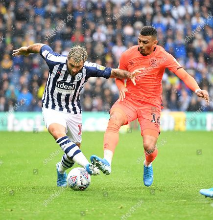 Charlie Austin of West Bromwich Albion is tackled by Karlan Grant of Huddersfield Town