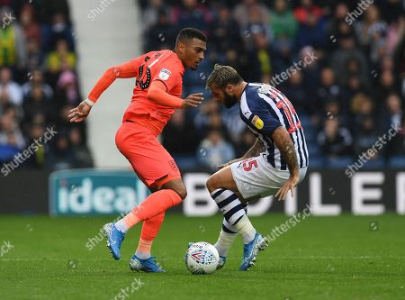 Karlan Grant of Huddersfield Town beats Charlie Austin of West Bromwich Albion