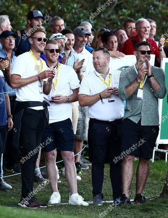 England cricketers Ben Stokes and Stuart Board watch the group of Danny Willett and Lee Westwood.
