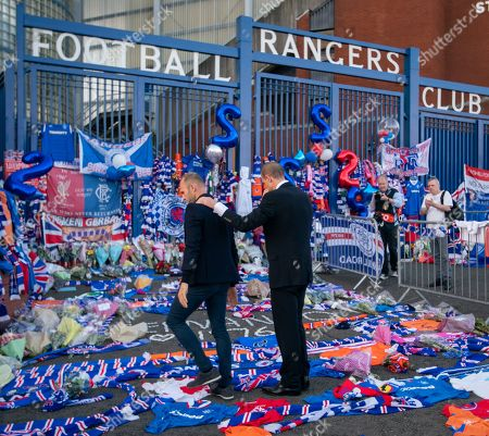 Stock Photo of Former Rangers team mates Gregory Vignal & Thomas Buffel lay a Rangers jersey with the number 2 on the back amongst flowers and scarves laid at the Copland Road gates outside Ibrox Stadium in tribute to former Rangers & Holland international footballer Fernando Ricksen who died yesterday after a 6 year battle with Motor Neurone Disease.