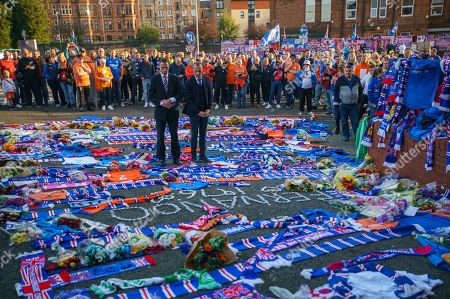 Stock Picture of Former Rangers team mates Gregory Vignal & Thomas Buffel lay a Rangers jersey with the number 2 on the back amongst flowers and scarves laid at the Copland Road gates outside Ibrox Stadium in tribute to former Rangers & Holland international footballer Fernando Ricksen who died yesterday after a 6 year battle with Motor Neurone Disease.