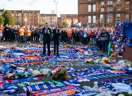 Stock Image of Former Rangers team mates Gregory Vignal & Thomas Buffel lay a Rangers jersey with the number 2 on the back amongst flowers and scarves laid at the Copland Road gates outside Ibrox Stadium in tribute to former Rangers & Holland international footballer Fernando Ricksen who died yesterday after a 6 year battle with Motor Neurone Disease.