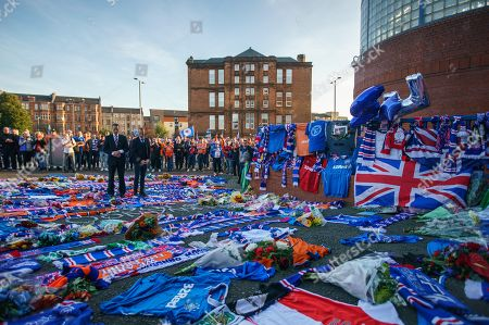 Former Rangers team mates Gregory Vignal & Thomas Buffel lay a Rangers jersey with the number 2 on the back amongst flowers and scarves laid at the Copland Road gates outside Ibrox Stadium in tribute to former Rangers & Holland international footballer Fernando Ricksen who died yesterday after a 6 year battle with Motor Neurone Disease.