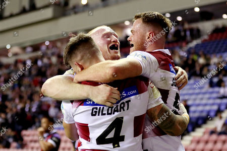 Oliver Gildart of Wigan Warriors celebrates scoring his sides first try with George Williams and Sam Burgess