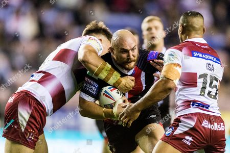 Gil Dudson of Salford Red Devils is tackled by  Liam Byrne and Willie Isa of Wigan Warriors