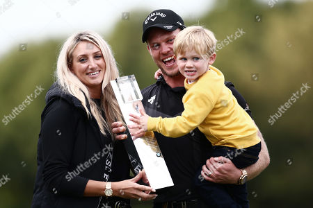 Danny Willett of England celebrates with the trophy and family.