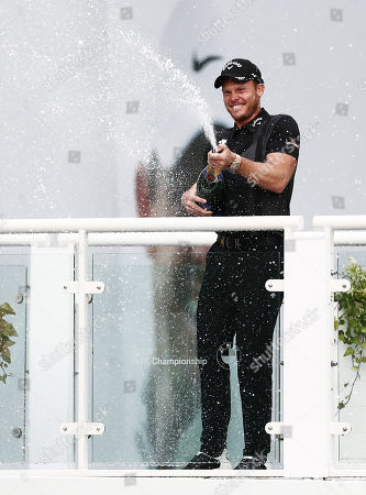 Danny Willett of England celebrates and sprays champagne.