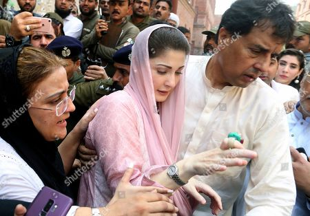 Muhammad Safdar, right, escorts his wife Maryam Nawaz, daughter of arrested former Prime Minister Nawaz Sharif, to an accountability court in Lahore, Pakistan, Wednesday, Sept.18, 2019. The court summoned her for using a bogus trust deed in the Avenfield properties case