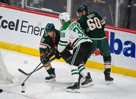 From the left; Minnesota Wild center Luke Johnson, Dallas Stars center Joel L'Esperance and Minnesota Wild defenseman Carson Soucy battle for control of the puck during the first period of a preseason NHL hockey game, in St. Paul, Minn. Dallas won 2-1 in overtime